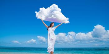 Lady on a beach holding a cloud