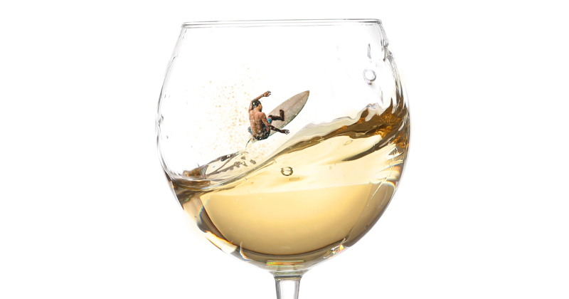 Man surfing in a a glass of wine
